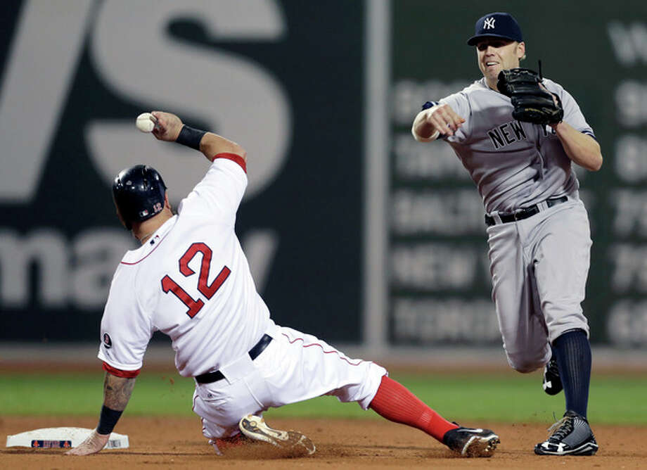 Boston Red Sox first baseman Mike Napoli (12) slides out on a fielder's choice as New York Yankees' Brendan Ryan, right, tries to throw to first base in the fourth inning of a baseball game at Fenway Park, in Boston, Sunday, Sept. 15, 2013. (AP Photo/Steven Senne) / AP