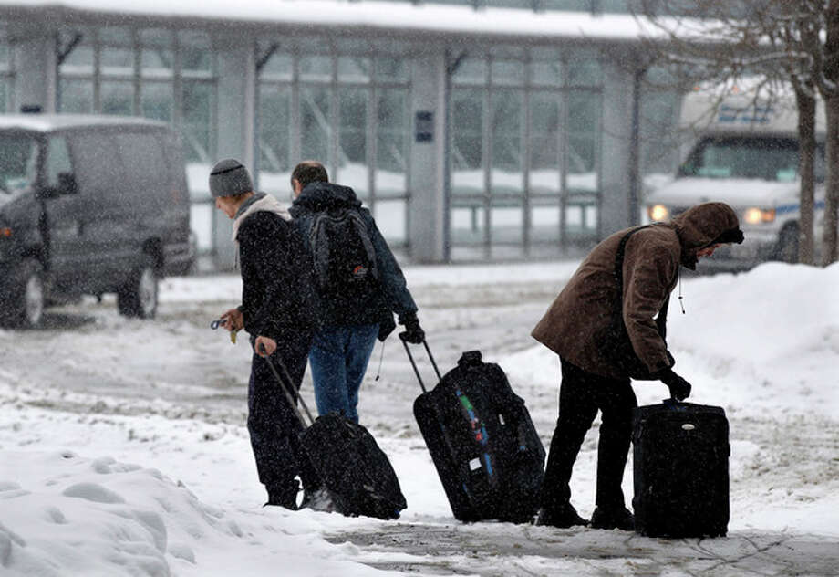 People walk in the snow at Buffalo Niagara International Airport in Buffalo, N.Y., Saturday, Dec. 29, 2012. A mild but widespread winter storm has developed over the Northeast and the upper Ohio River Valley, the second in less than a week for the regions. (AP Photo/Mel Evans) / AP
