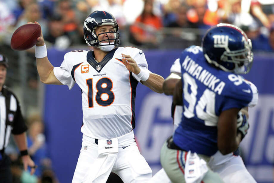 Denver Broncos quarterback Peyton Manning (18) throws a pass during the first half of an NFL football game as New York Giants linebacker Mathias Kiwanuka (94) rushes the passer Sunday, Sept. 15, 2013, in East Rutherford, N.J. (AP Photo/Kathy Willens) / AP