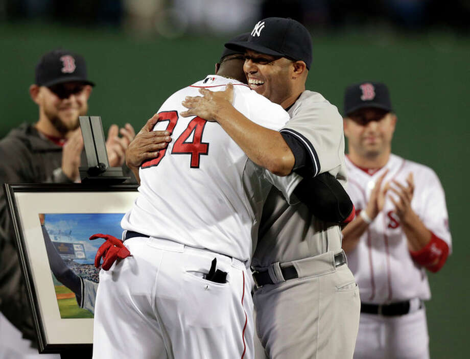 New York Yankees relief pitcher Mariano Rivera, right, hugs Boston Red Sox's David Ortiz during a tribute for Rivera before the start of a baseball game at Fenway Park, in Boston, Sunday, Sept. 15, 2013. (AP Photo/Steven Senne) / AP