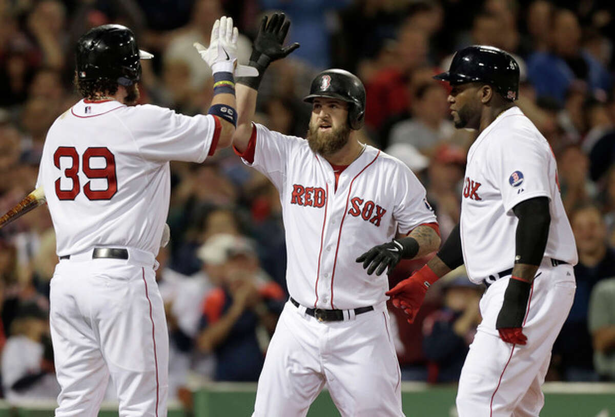 Boston Red Sox's Mike Napoli, center, celebrates with teammates Jarrod Saltalamacchia, left, and David Ortiz, right, after hitting a two-run home run off a pitch by New York Yankees' Ivan Nova in the first inning of a baseball game at Fenway Park, in Boston, Sunday, Sept. 15, 2013. (AP Photo/Steven Senne)