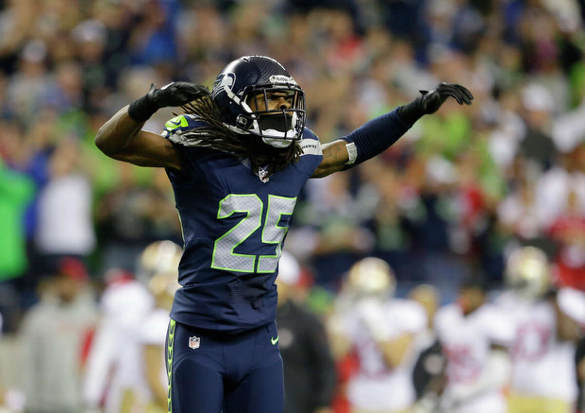 Seattle Seahawks' Richard Sherman celebrates after the Seahawks score a safety in the first half of an NFL football game against the San Francisco 49ers, Sunday, Sept. 15, 2013, in Seattle. (AP Photo/Elaine Thompson)