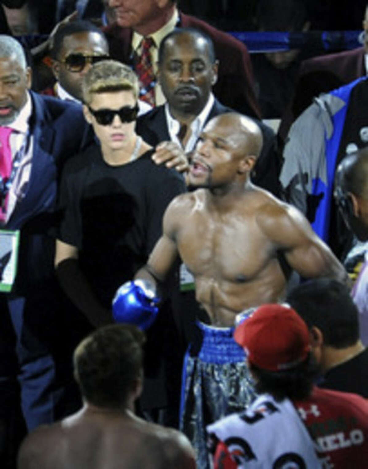 In this photo provided by the Las Vegas News Bureau, Justin Bieber stands with Floyd Mayweather Jr. in the ring prior to Mayweather?'s super welterweight title fight against ?