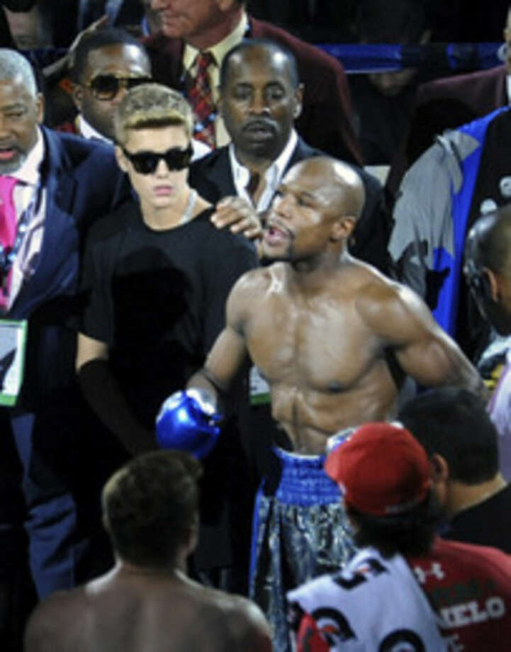 "In this photo provided by the Las Vegas News Bureau, Justin Bieber stands with Floyd Mayweather Jr. in the ring prior to Mayweather's super welterweight title fight against ""Canelo"" Alvarez at the MGM Grand Garden Arena in Las Vegas Saturday, Sept. 14, 2013. (AP Photo/Las Vegas News Bureau, Brian Jones)"