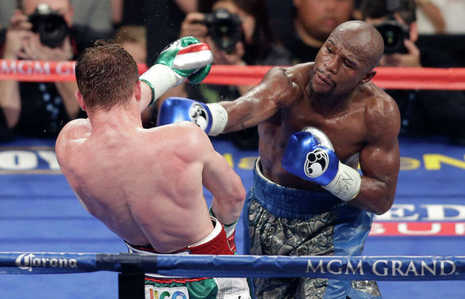 Floyd Mayweather Jr. throws a punch against Canelo Alvarez during a 152-pound title fight, Saturday, Sept. 14, 2013, in Las Vegas. (AP Photo/Isaac Brekken) / FR159466 AP