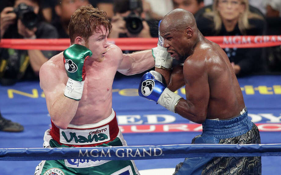 Canelo Alvarez, left, throws a punch against Floyd Mayweather Jr. during a 152-pound title fight, Saturday, Sept. 14, 2013, in Las Vegas. (AP Photo/Isaac Brekken) / FR159466 AP