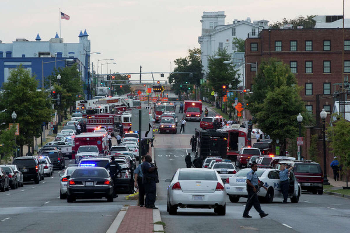 Police work the scene on M Street, SE in Washington, where a gunman was reported at the Washington Navy Yard in Washington, on Monday, Sept. 16, 2013. The U.S. Navy says one person is injured after a shooting at a Navy building in Washington. (AP Photo/Jacquelyn Martin)