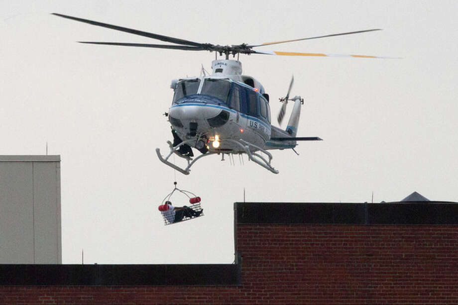 A U.S. Park Police helicopter removes a man in a basket from the Washington Navy Yard Monday, Sept. 16, 2013. Earlier in the day, the U.S. Navy said it was searching for an active shooter at the Naval Sea Systems Command headquarters, where about 3,000 people work. The exact number of people killed and the conditions of those wounded was not immediately known. (AP Photo/Jacquelyn Martin) / AP