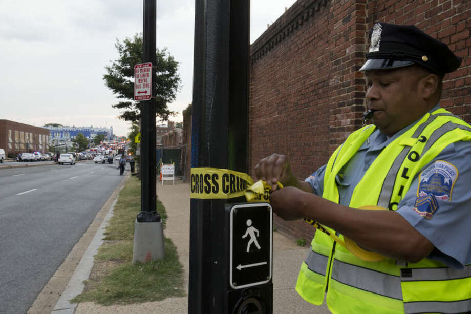 Police work the scene on M Street S.E. in Washington, where a gunman was reported in a military building at the Washington Navy Yard Monday, Sept. 16, 2013. Shots have been fired and employees directed to a shelter. Police and federal agents from multiple law enforcement agencies responded to the scene and streets in the area were closed. (AP Photo/Jacquelyn Martin)