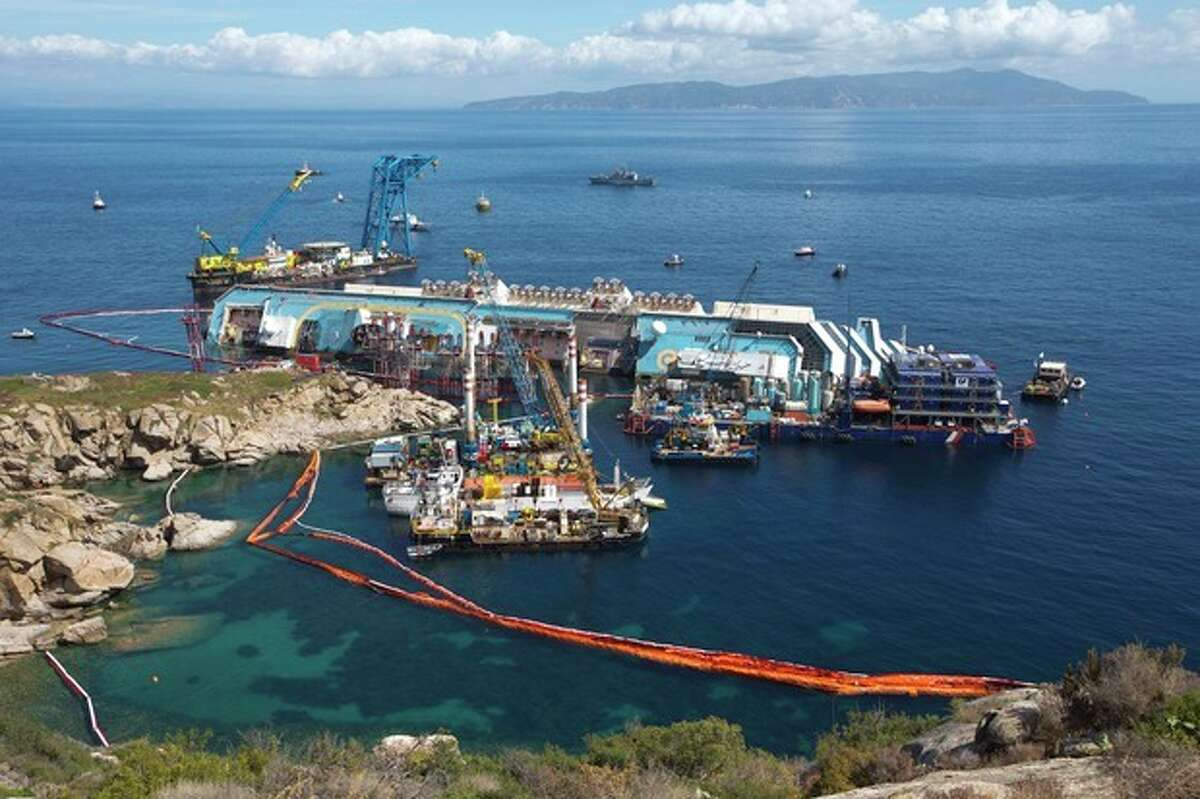The Costa Concordia ship lies on its side on the Tuscan Island of Giglio, Italy,Monday, Sept. 16, 2013. An international team of engineers is trying a never-before attempted strategy to set upright the luxury liner, which capsized after striking a reef in 2012 killing 32 people. (AP Photo/Andrew Medichini)