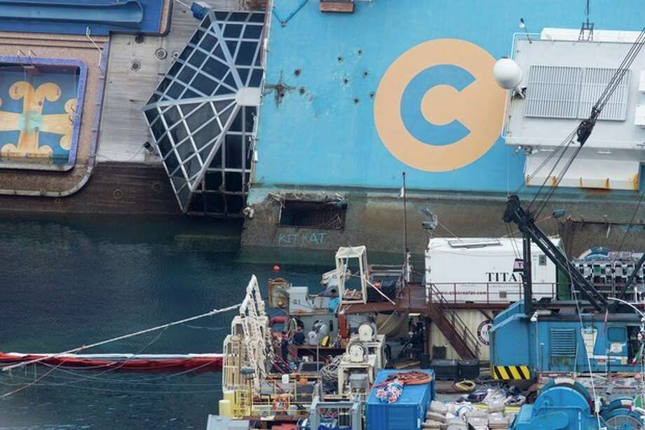 The Costa Concordia ship lies on its side on the Tuscan Island of Giglio, Italy, Monday, Sept. 16, 2013. An international team of engineers is trying a never-before attempted strategy to set upright the luxury liner, which capsized after striking a reef in 2012 killing 32 people. (AP Photo/Andrew Medichini) / AP