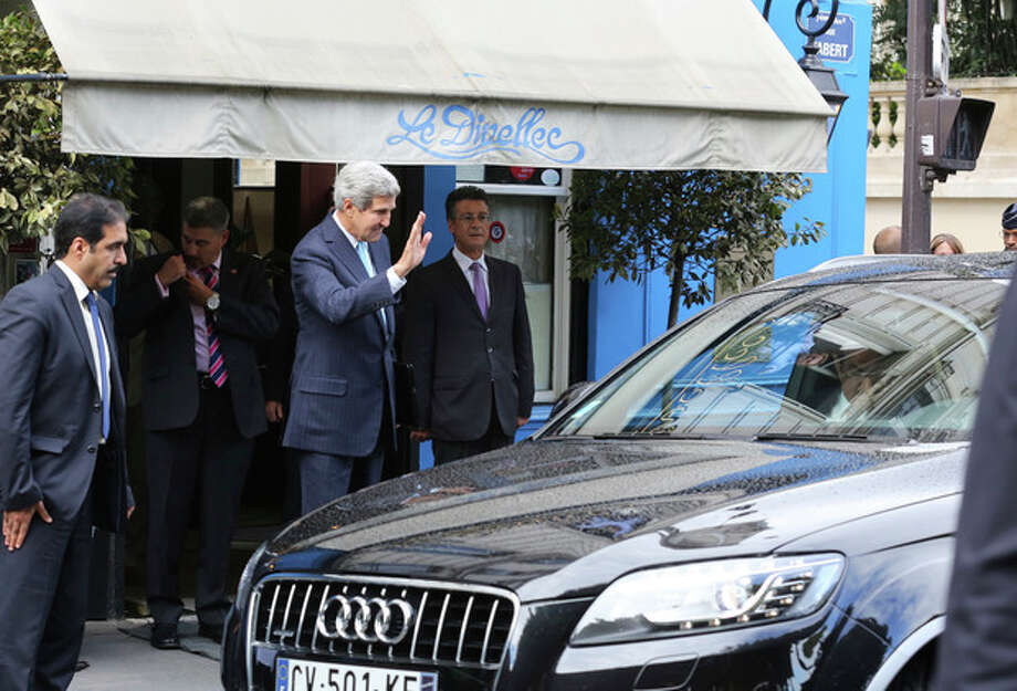 U.S. Secretary of State John Kerry waves a goodbye to Saudi foreign minister Prince Saud Al-Faisal Bin Abdul Aziz, unseen, in his car, right, following their working lunch in a Paris restaurant, Monday Sept. 16, 2013. The U.S. and its closest allies laid out a two-pronged approach in Syria on Monday, calling for enforceable U.N. benchmarks for eradicating the country's chemical weapons program and an international conference bolstering the moderate opposition. (AP Photo/Remy de la Mauviniere) / AP