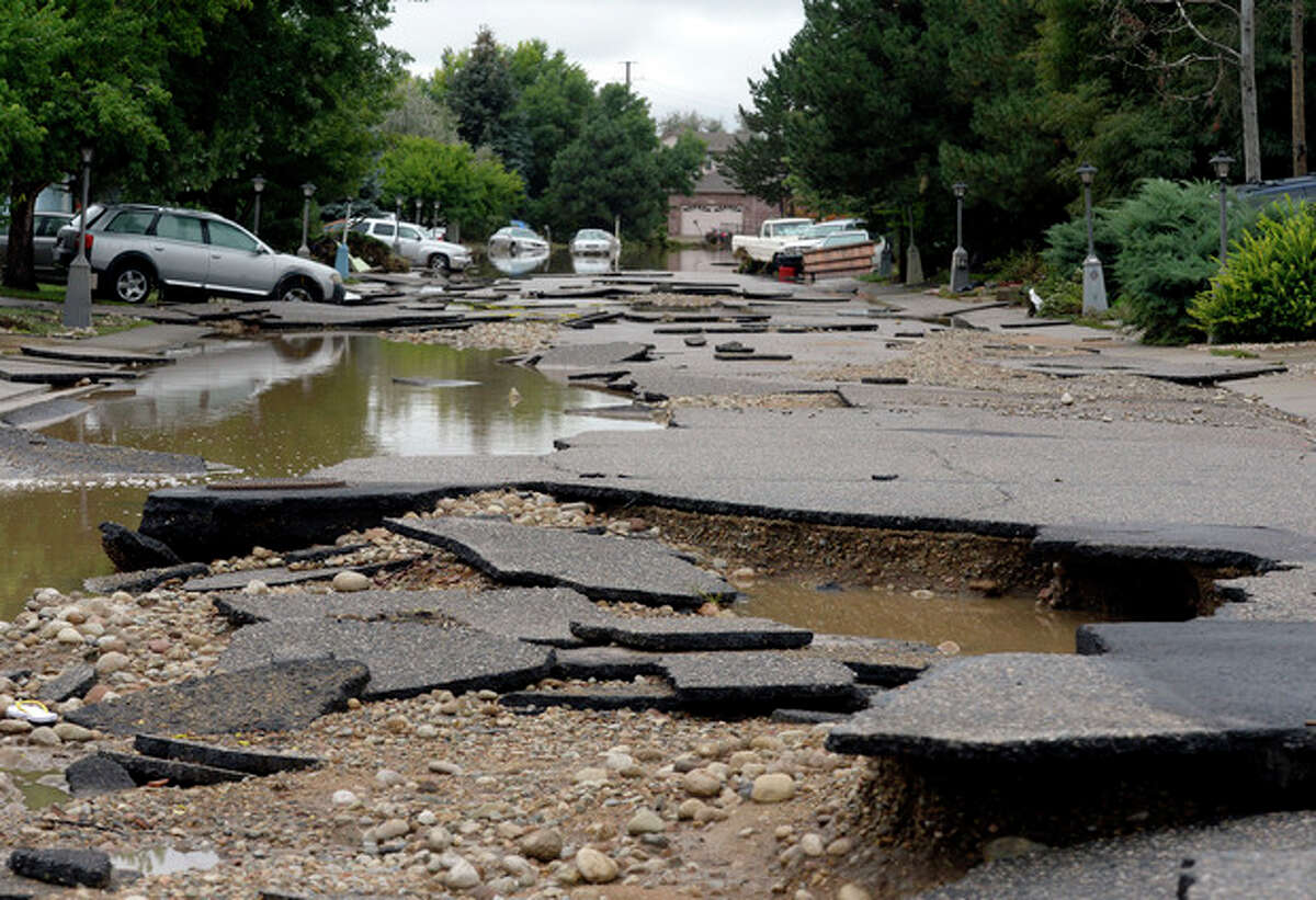Hayden Court collapsed during the flooding of the Troxell neighborhood in Longmont, Colo., Sunday Sept. 15, 2013. Evacuations are underway Sunday morning in some Longmont neighborhoods because the St. Vrain River is rising quickly. (AP Photo/Denver Post, Craig F. Walker)