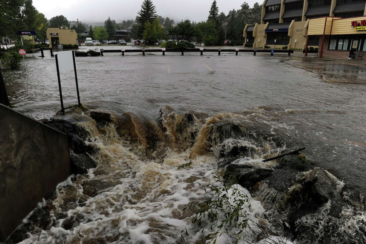 A heavy flow of water pours out of a parking lot on E. Elkhorn Ave. overwhelming a culvert heading under the roadway. As a steady rain continues to fall, the town of Estes Park, Colo., begins Sunday Sept. 15, 2013 to clean up the flooded downtown streets and stores that are popular for visitors. (AP Photo/ The Denver Post, Kathryn Scott Osler)
