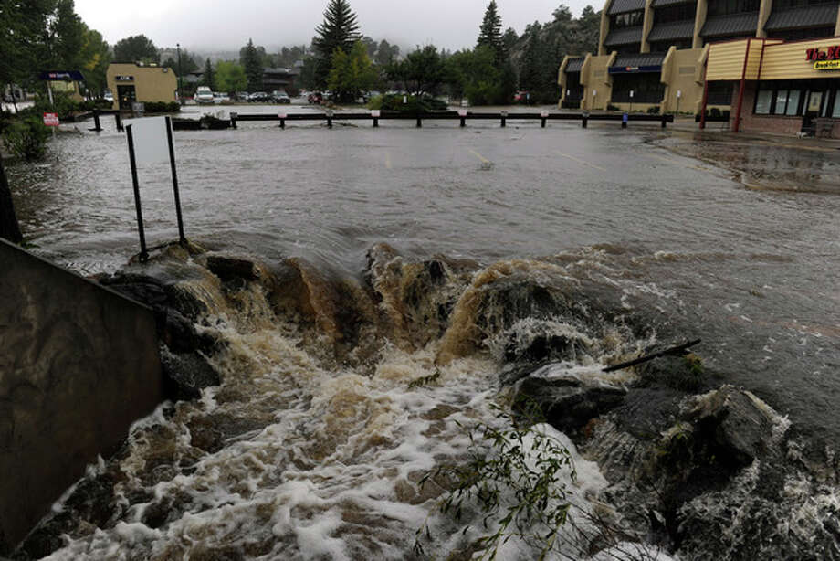 A heavy flow of water pours out of a parking lot on E. Elkhorn Ave. overwhelming a culvert heading under the roadway. As a steady rain continues to fall, the town of Estes Park, Colo., begins Sunday Sept. 15, 2013 to clean up the flooded downtown streets and stores that are popular for visitors. (AP Photo/ The Denver Post, Kathryn Scott Osler) / The Denver Post