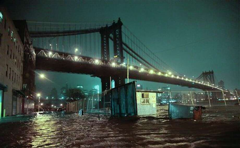 FILE - In this Oct. 29, 2012 file photo, streets in the Brooklyn borough of New York are flooded under the Manhattan Bridge as a surge of seawater is pushed into New York City by Superstorm Sandy. The weather in 2012 was deadly, costly and record-breaking everywhere _ but especially in the United States. (AP Photo/Bebeto Matthews, File) / AP