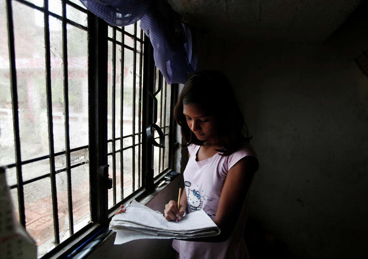 In this Saturday, Sept. 14, 2013 photo, Sushma Verma, 13, does her homework at her house in Lucknow, India. Verma, from a poor family in north India, enrolled in a master's degree in microbiology, after her father sold his land to pay for some of his daughter's tuition in the hope of catapulting her into India's growing middle class. Verma finished high school at 7 and earned an undergraduate degree at age 13 - milestones she said were possible only with the sacrifices and encouragement of her uneducated and impoverished parents. (AP Photo/Rajesh Kumar Singh)