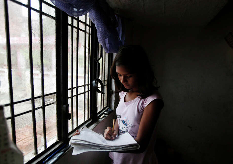 In this Saturday, Sept. 14, 2013 photo, Sushma Verma, 13, does her homework at her house in Lucknow, India. Verma, from a poor family in north India, enrolled in a master's degree in microbiology, after her father sold his land to pay for some of his daughter's tuition in the hope of catapulting her into India's growing middle class. Verma finished high school at 7 and earned an undergraduate degree at age 13 - milestones she said were possible only with the sacrifices and encouragement of her uneducated and impoverished parents. (AP Photo/Rajesh Kumar Singh) / AP