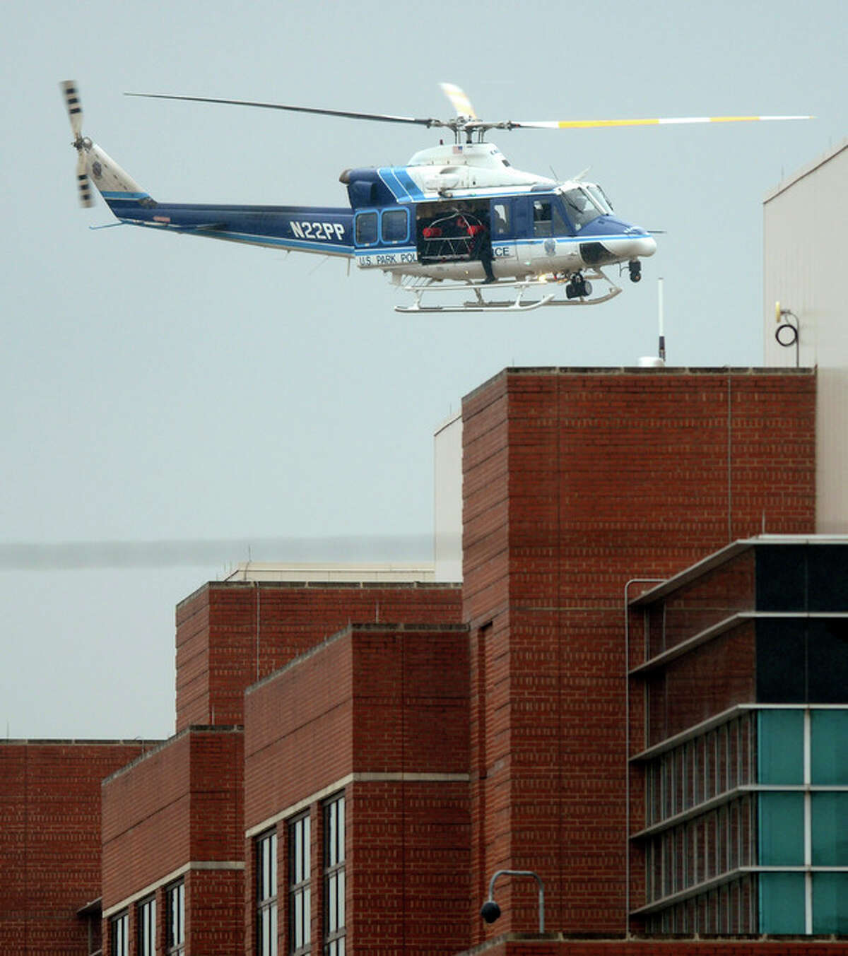 A U.S. Park Police helicopter flies over a building at the Washington Navy Yard in Washington, Monday, Sept. 16, 2013. At least one gunman opened fire inside a building at the Washington Navy Yard on Monday morning, (AP Photo/Susan Walsh)