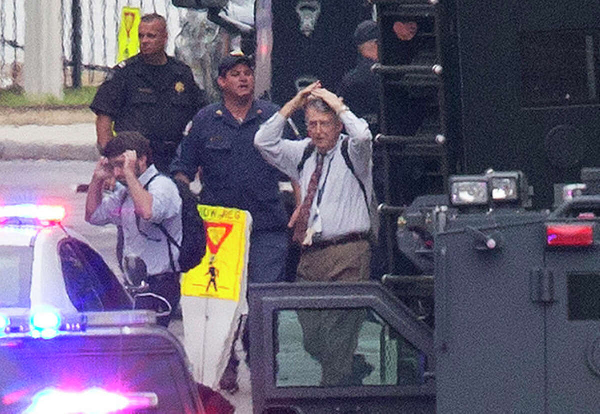 People hold their hands to their heads as they are escorted out of the building where a deadly shooting rampage occurred at the Washington Navy Yard in Washington, Monday, Sept. 16, 2013. One shooter was killed, but police said they were looking for two other possible gunmen wearing military-style uniforms. (AP Photo/Jacquelyn Martin)