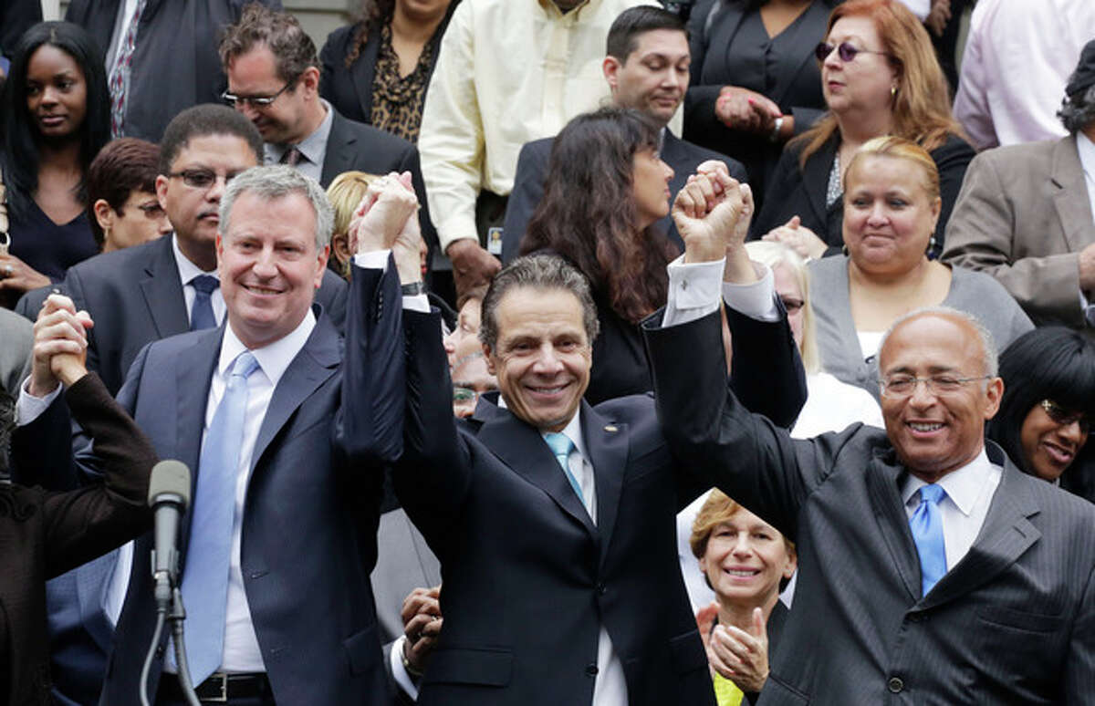 New York Governor Andrew Cuomo, center, raises the hands of Democratic mayoral candidates Bill de Blasio, left, and Bill Thompson on the steps of City Hall, Monday, Sept. 16, 2013 in New York. Thompson conceded to de Blasio, avoiding a runoff election in the Democratic primary, leaving de Blasio to face Republican candidate Joe Lhota in the Nov. 5 election. (AP Photo/Mark Lennihan)