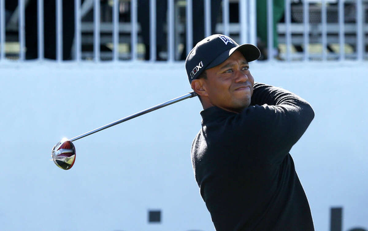 Tiger Woods watches his tee shot on the first hole during the final round of the BMW Championship golf tournament at Conway Farms Golf Club in Lake Forest, Ill., Monday, Sept. 16, 2013. (AP Photo/Charles Rex Arbogast)