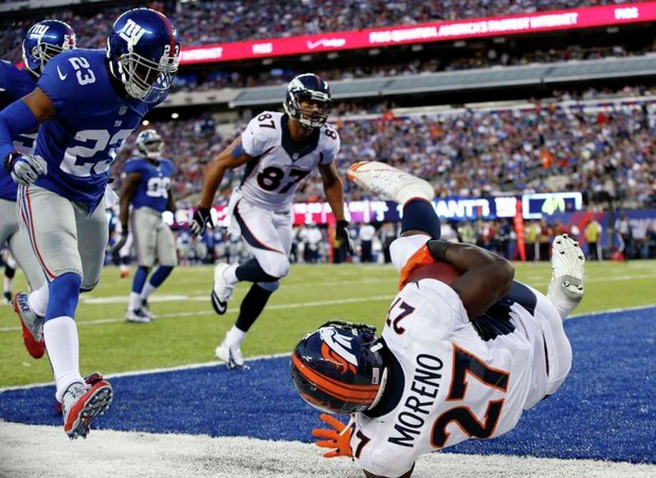 Denver Broncos running back Knowshon Moreno (27) dives for a touchdown in front of New York Giants cornerback Corey Webster (23) as teammate Eric Decker (87) trails the play during the second half of an NFL football game Sunday, Sept. 15, 2013, in East Rutherford, N.J. (AP Photo/Kathy Willens) / AP