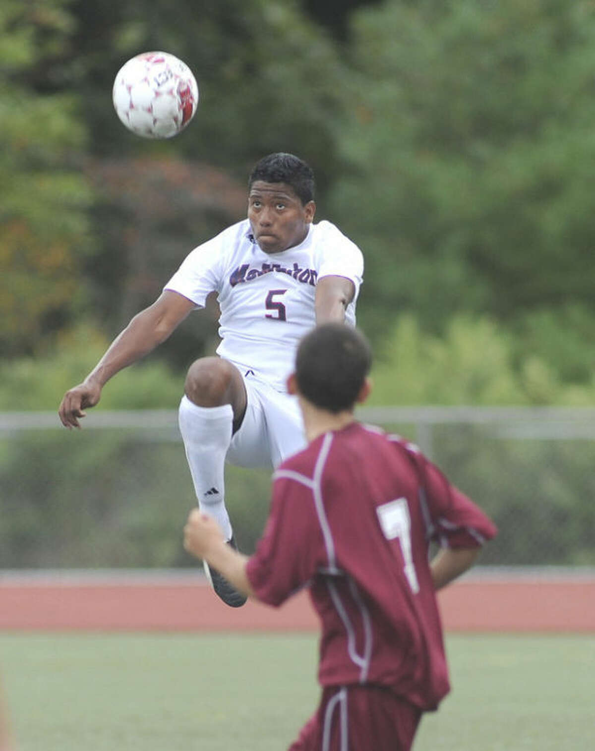 Hour photo/John Nash Kelvin Medina of the Brien McMahon boys soccer team goes airborne to volley a ball out of the air during Monday's FCIAC boys soccer game against St. Joseph. The visiting Cadets won 1-0.