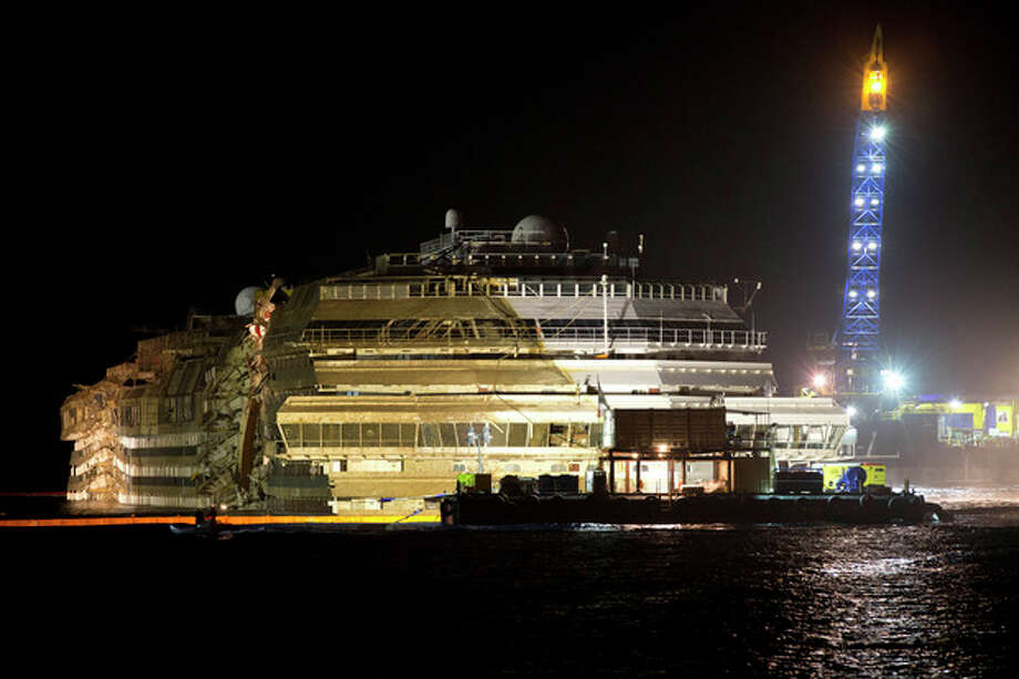 """The Costa Concordia is seen after it was lifted upright, on the Tuscan Island of Giglio, Italy, early Tuesday morning, Sept. 17, 2013. The crippled cruise ship was pulled completely upright early Tuesday after a complicated, 19-hour operation to wrench it from its side where it capsized last year off Tuscany, with officials declaring it a """"perfect"""" end to a daring and unprecedented engineering feat. (AP Photo/Andrew Medichini) / AP"""