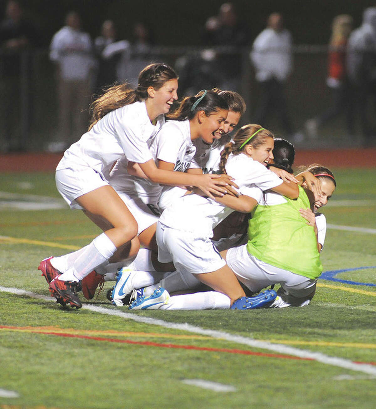 Hour photo/John Nash Members of the Norwalk High girls soccer team pile on goalkeeper Jasmine Kishimoto after the Bears defeated cross-town rival Brien McMahon 1-0 on Monday night.