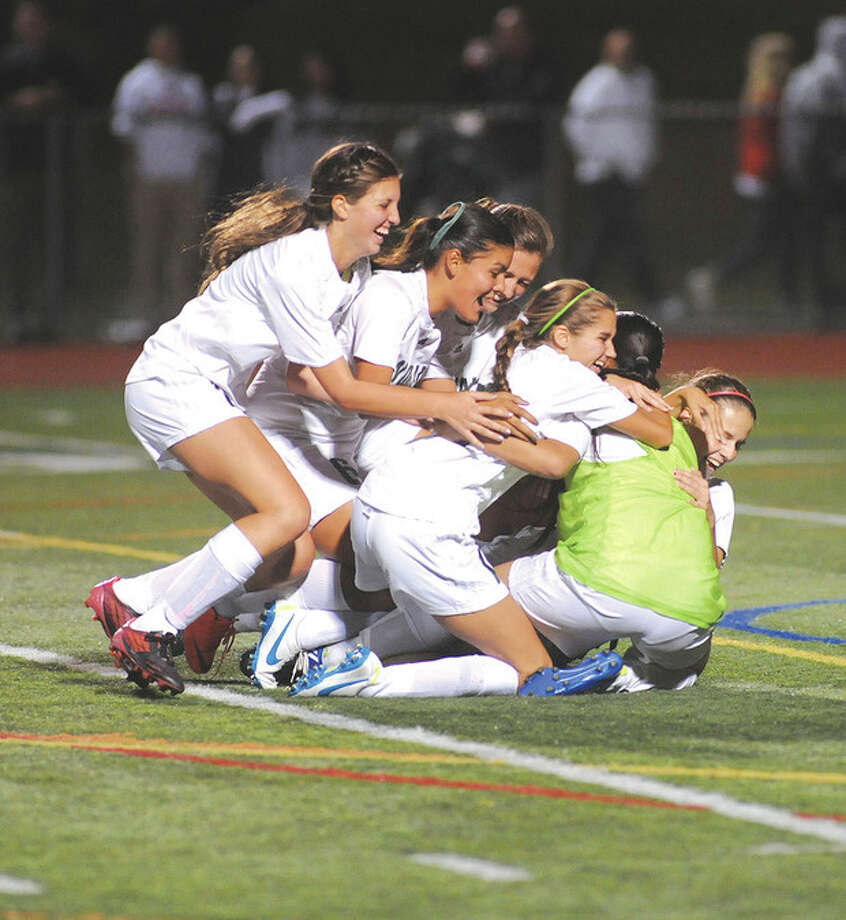Hour photo/John NashMembers of the Norwalk High girls soccer team pile on goalkeeper Jasmine Kishimoto after the Bears defeated cross-town rival Brien McMahon 1-0 on Monday night.