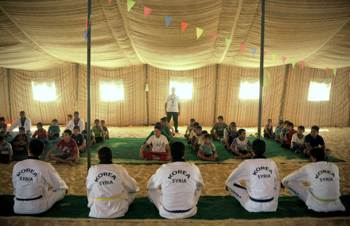 Syrian refugee children look at Korean and Syrian Taekwondo instructors during training at Zaatari refugee camp, near Mafraq, Jordan, Tuesday, Sept. 17, 2013. Koreans are also training adult refugees to give classes themselves to the children, who make up a majority of the camp, home to 120,000 Syrians who fled the military onslaught of President Bashar Assad. (AP Photo/Bela Szandelszky)
