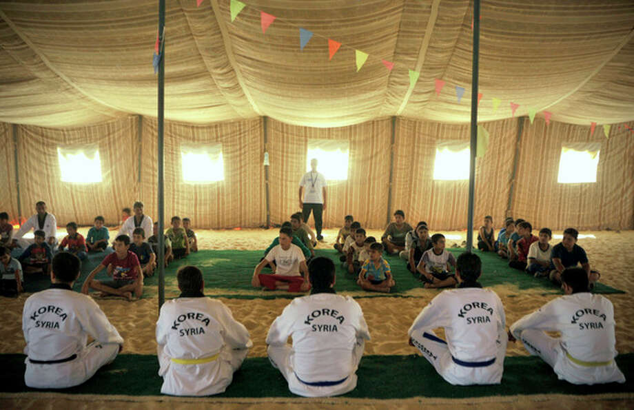 Syrian refugee children look at Korean and Syrian Taekwondo instructors during training at Zaatari refugee camp, near Mafraq, Jordan, Tuesday, Sept. 17, 2013. Koreans are also training adult refugees to give classes themselves to the children, who make up a majority of the camp, home to 120,000 Syrians who fled the military onslaught of President Bashar Assad. (AP Photo/Bela Szandelszky) / AP