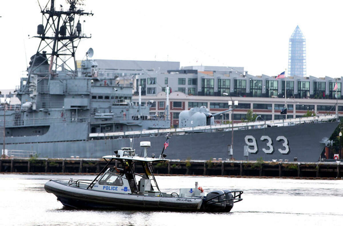A police boat patrols near the scene of a shooting at the Washington Navy Yard on Monday, Sept. 16, 2013, in Washington. At least one gunman opened fire inside a building at the Washington Navy Yard on Monday morning. (AP Photo/ Evan Vucci)