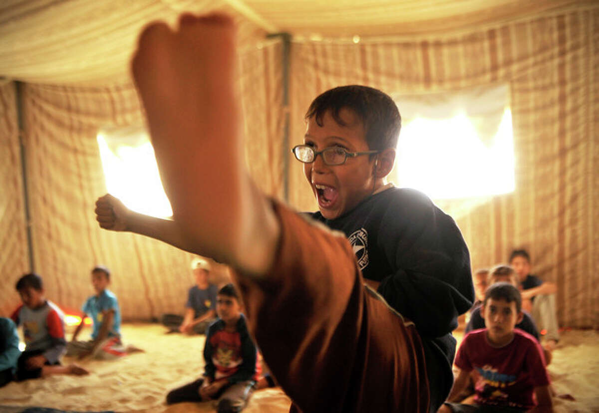 A Syrian refugee boy practices Taekwondo during training at Zaatari refugee camp, near Mafraq, Jordan, Tuesday, Sept. 17, 2013. Korean Taekwondo masters are also training adult refugees to give classes themselves to the children, who make up a majority of the camp, home to 120,000 Syrians who fled the military onslaught of President Bashar Assad. (AP Photo/Bela Szandelszky)
