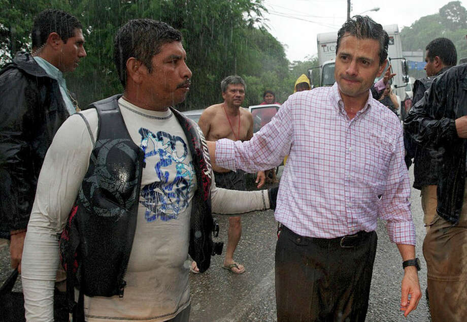 In this photo released by Mexico's presidential press office, Mexico's President Enrique Pena Nieto speaks to a resident affected by Tropical Storm Manuel as it rains in the Pacific coast city of Acapulco, Mexico, Monday, Sept. 16, 2013. Pena Nieto toured the disaster zone on Monday and ordered efforts to reopen the highway that connects the port city to Mexico City after twin storms left scenes of havoc on both of Mexico's coasts. (AP Photo/Presidencia de Mexico) / Presidencia de Mexico