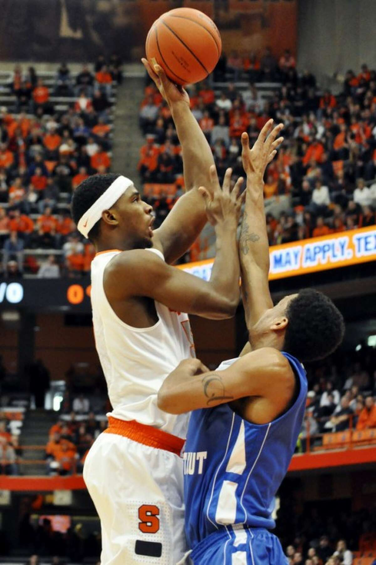 Syracuse's C. J. Fair shoots over Central Connecticut State's Adonis Burbage during the first half of an NCAA college basketball game in Syracuse, N.Y., Monday, Dec. 31, 2012. (AP Photo/Kevin Rivoli)
