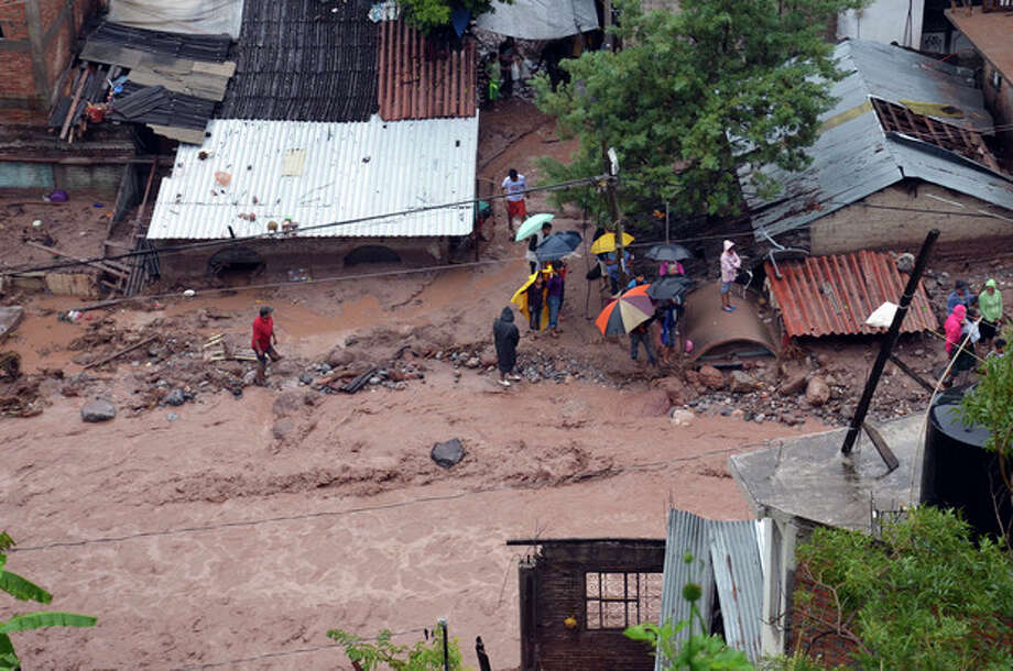 People stand next to damaged homes after a landslide caused by heavy rains came down on a low income neighborhood in the city of Chilpancingo, Mexico, Monday Sept. 16, 2013. Tropical Storm Ingrid and remnants of Tropical Storm Manuel drench Mexico's Gulf and Pacific coasts, flooding towns and cities in a national emergency that federal authorities say has caused at least 34 deaths. (AP Photo/Alejandrino Gonzalez) / AP