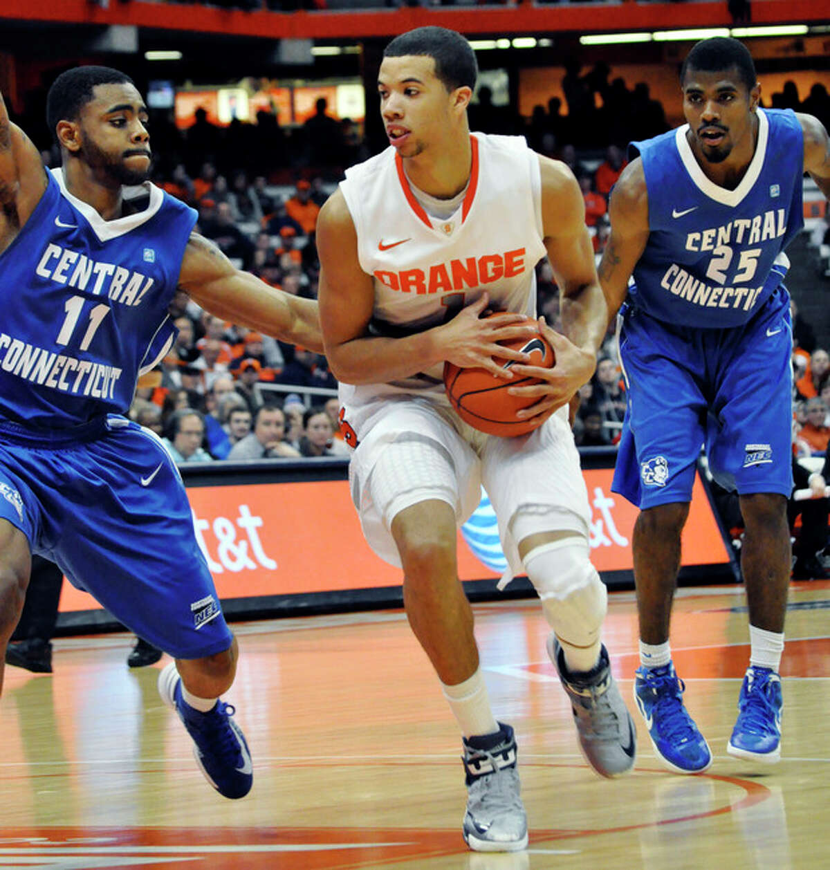 Syracuse's Michael Carter-Williams drives against Central Connecticut State's Malcolm McMillan, left, as Matt Hunter, right, watches during the second half of an NCAA college basketball game in Syracuse, N.Y., Monday, Dec. 31, 2012. Syracuse won 96-62. (AP Photo/Kevin Rivoli)