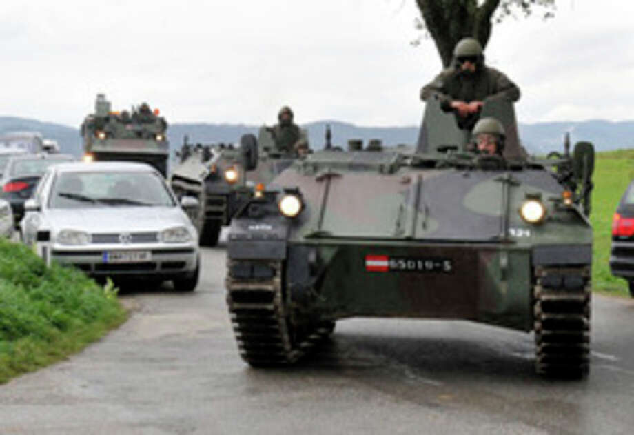 Austrian army soldiers in armored vehicles arrive near the villages of Grosspriel and Kollapriel some 90 kilometers (55 miles) west of Vienna, Austria, Tuesday, Sept. 17, 2013, where a man is barricading himself inside a farm building after he killed two police officers and the driver of an emergency rescue vehicle as the dpa news agency said, citing an unidentified police spokesman. Interior Minister spokesman Karl-Heinz Grundboeck said a third police officer was apparently being held by the shooter in the village of Kollapriel. He confirmed that three people were shot but refused to say whether their injuries were fatal, explaining that officials did not want to give the gunman information through news reports he was likely monitoring. (AP Photo/Hans Punz) / AP