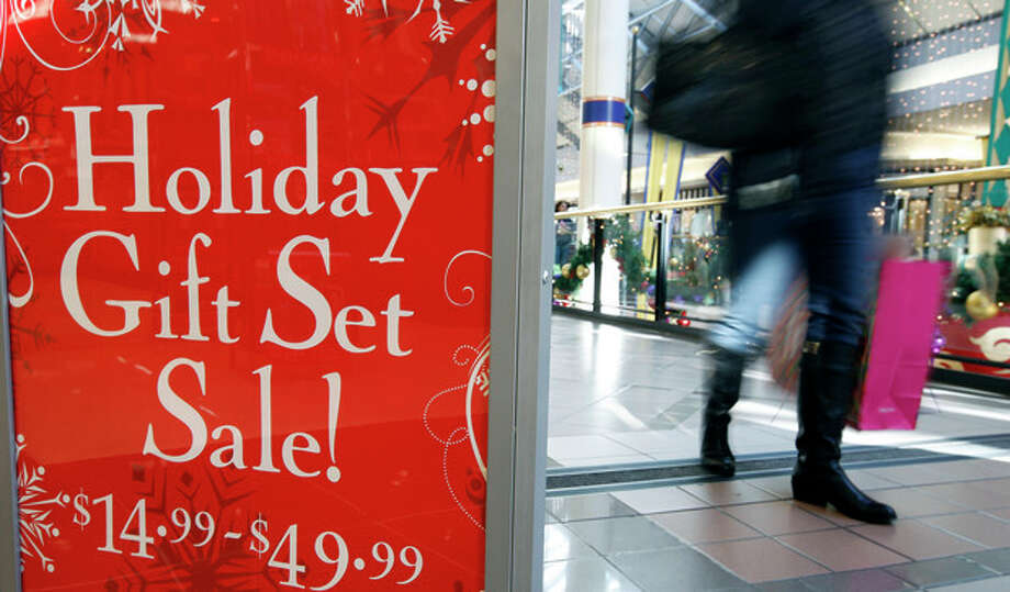 FILE - In this Monday, Dec. 24, 2012, file photo, a retail store at the CambridgeSide Galleria mall in Cambridge, Mass., advertises holiday sale. Coming off of a weak back-to-school shopping period, a research firm said Thursday, Sept. 17, 2013, that holiday sales growth will be slower this year during the crucial holiday season. Shoppers are also expected to visit fewer stores as they research purchases online. (AP Photo/Michael Dwyer, File) / AP