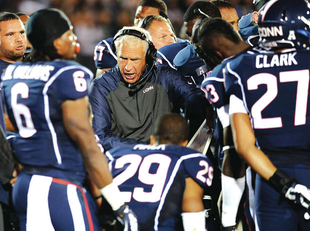 AP photo UConn head coach Paul Pasqualoni, center, talks to his players during Saturday's loss to Maryland. The Huskies are 0-2, but Pasqualoni says the prospect of playing Michigan at home should get his players' juices flowing.