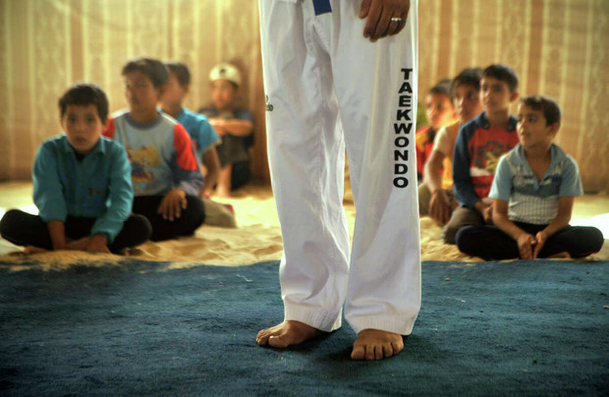 Syrian refugee children sit behind their Taekwondo instructor during training at Zaatari refugee camp, near Mafraq, Jordan, Tuesday, Sept. 17, 2013. Korean Taekwondo masters are also training adult refugees to give classes themselves to the children, who make up a majority of the camp, home to 120,000 Syrians who fled the military onslaught of President Bashar Assad. (AP Photo/Bela Szandelszky)