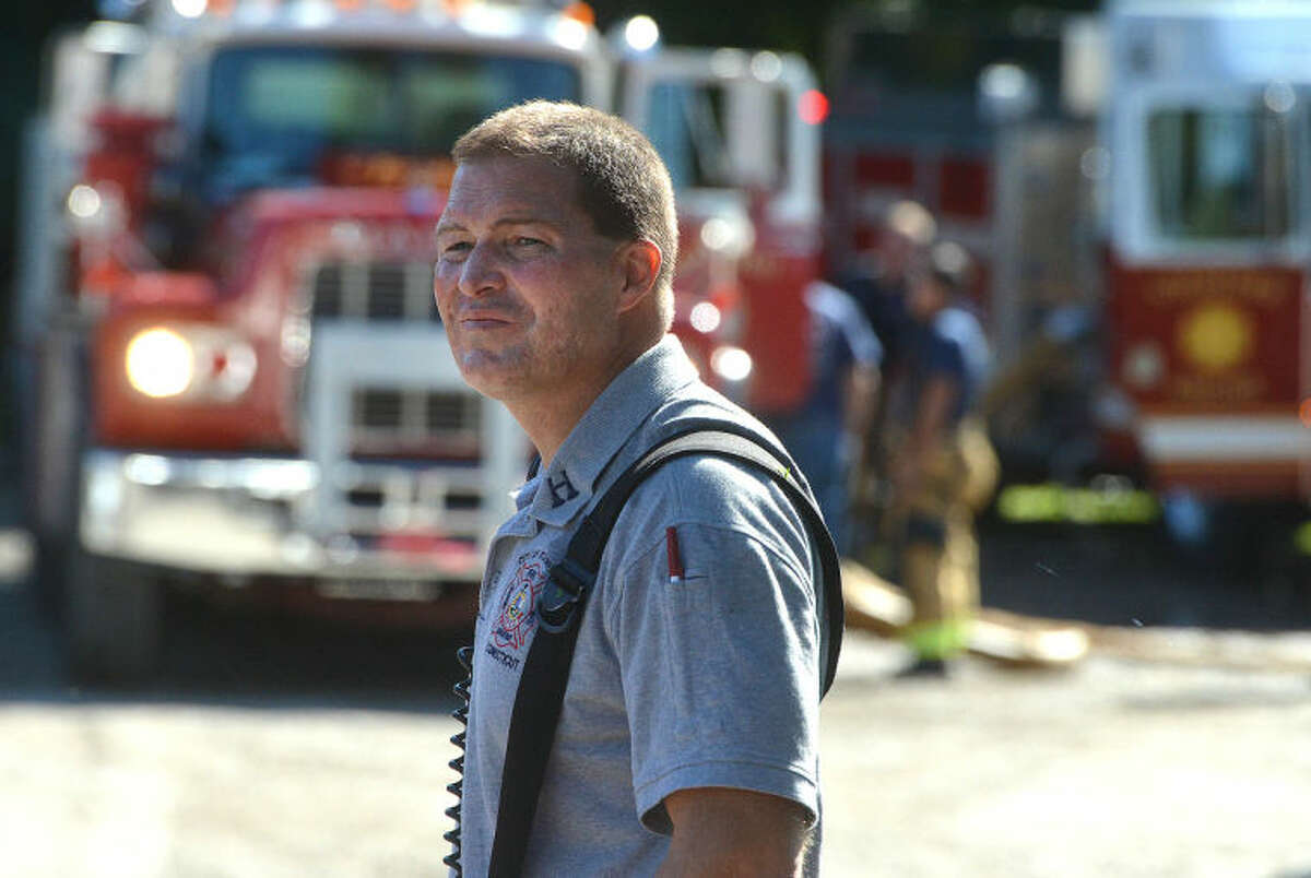 Hour Photo/Alex von Kleydorff A Stamford Firefighter looks for Fire Department Tanker trucks from surrounding towns to fill with water from Holts pond on Long Ridge Rd. and send to the house explosion