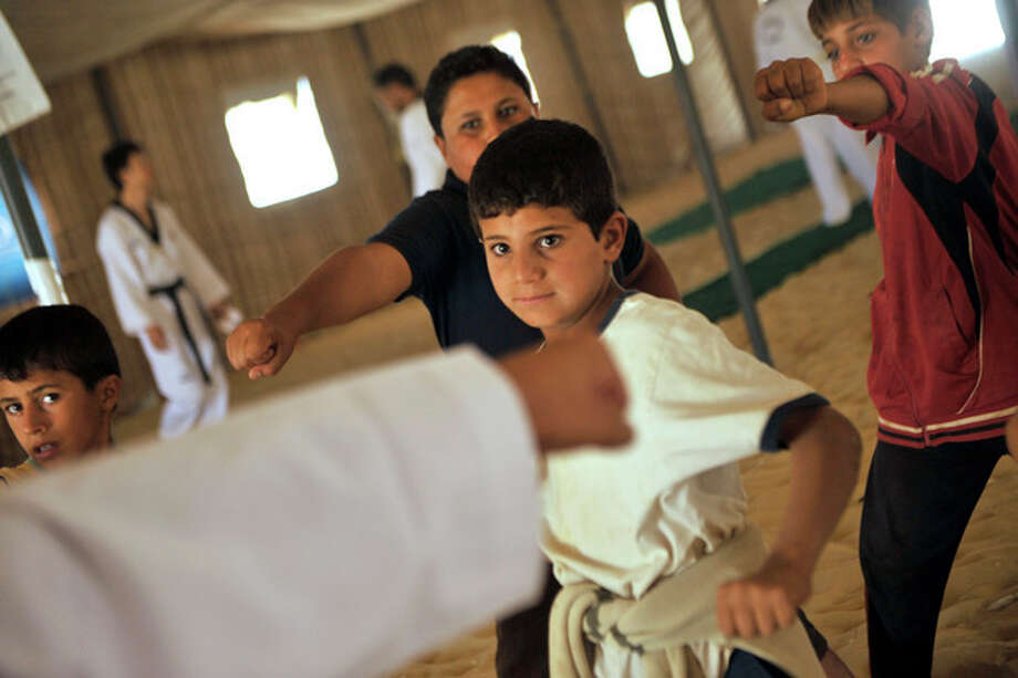 Syrian refugee children look at their Korean Taekwondo instructor during training at Zaatari refugee camp, near Mafraq, Jordan, Tuesday, Sept. 17, 2013. Koreans are also training adult refugees to give classes themselves to the children, who make up a majority of the camp, home to 120,000 Syrians who fled the military onslaught of President Bashar Assad. (AP Photo/Bela Szandelszky) / AP