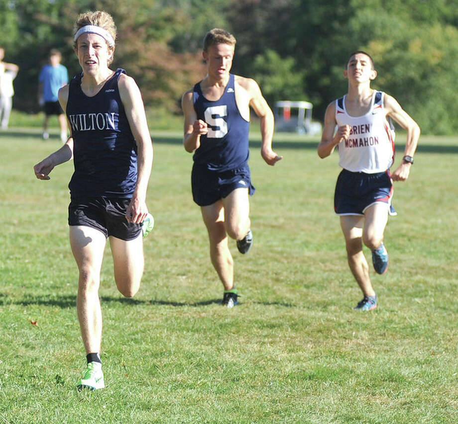 Hour photo/John NashSpencer Brown of Wilton, left, holds off the finishing kick of Staples' Oliver Hickson, center, and Eric van der Els of Brien McMahon to win Tuesday's multi-team cross country meet at Waveny Park in New Canaan, The threesome finished within two seconds of each other with Brown winning in 16 minutes, eight seconds.