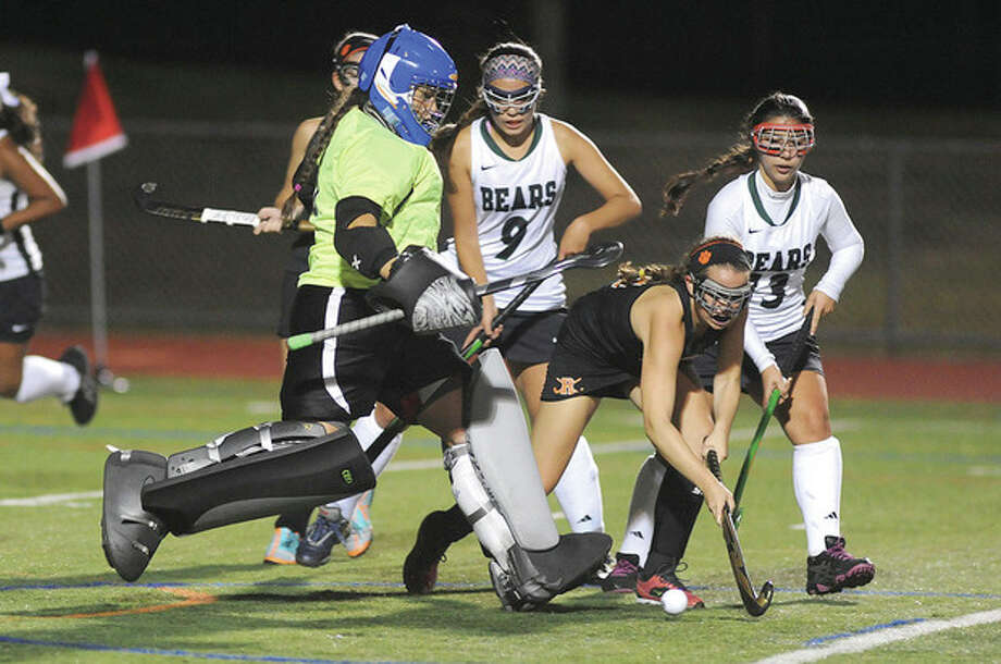 Hour photo/John NashNorwalk's Shannon O'Malley, left, comes out of goal to kick the ball away from Ridgefield's Claire Watsik as Norwalk defenders Madeline Mannella (9) and Lizzie Savaides (13) look on.