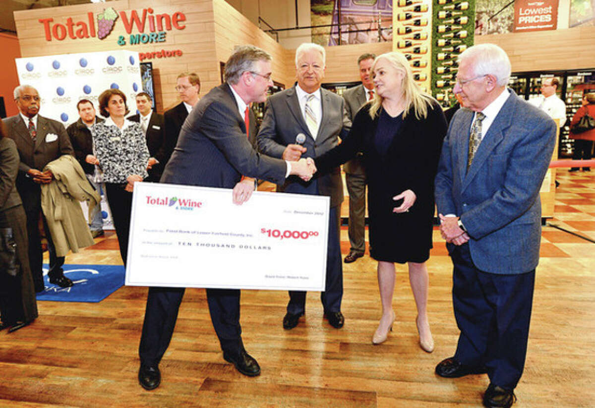 Hour photos / Erik Trautmann Total Wine & More co-owner David Trone and Norwalk Mayor Richard Moccia thank Food Bank Executive Director Kate Lombardo and Food Bank Board Chairman Sam Cingari while Total Wine presents to the Food Bank of Lower Fairfield County a check for $10,000 during the liquor store's grand opening on Main Avenue in Norwalk on Thursday evening. Below, one of the many long wine aisles.