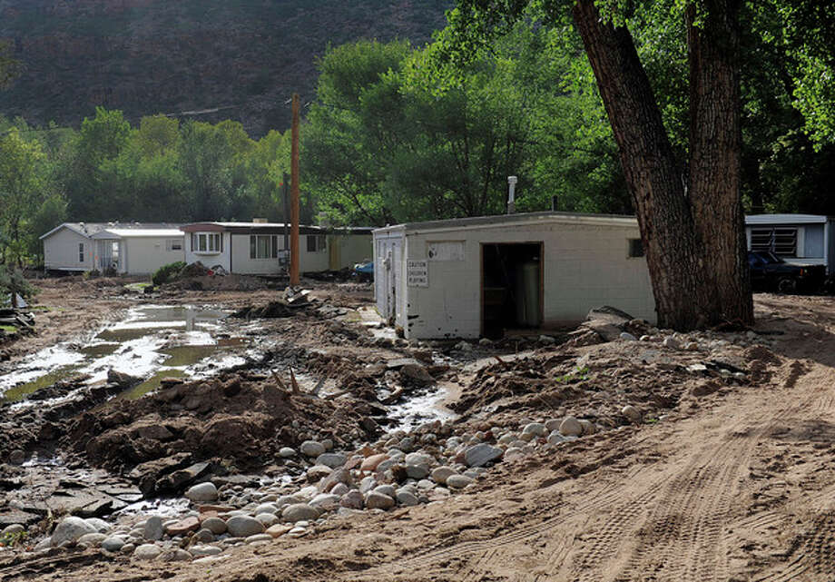 Flood damage is seen at the River Bend Mobile Home Park in Lyons, Colo., on Thursday, Sept. 19, 2013. Hundreds of evacuees were allowed past National Guard roadblocks Thursday to find a scene of tangled power lines, downed utility poles, and mud-caked homes and vehicles. (AP Photo/Chris Schneider) / FR170036 AP