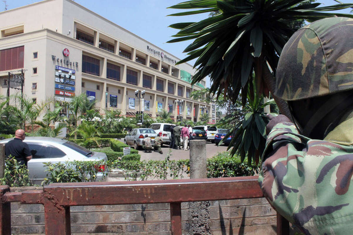 A soldier aims his weapon outside the Westgate Mall, an upscale shopping mall in Nairobi, Kenya Saturday Sept. 21 2013, where shooting erupted when armed men staged an attack. A witness to the attacks at Nairobi's upscale mall says that gunmen told Muslims to stand up and leave and that non-Muslims would be targeted. Initial police reports had described the incident as a botched robbery. Witnesses say a half dozen grenades also went off along with volleys of gunfire in and around the mall. (AP Photo/Jason Straziuso)